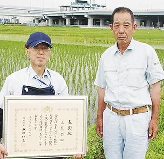 豊かな水田を背に、鈴木代表(左)と三堀さん