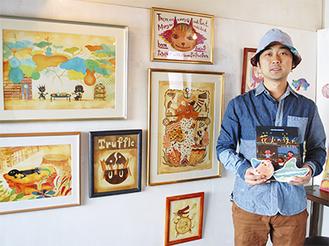 絵本を手にする佐々木さん。自身が手掛けた作品とともに