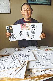 集めたサインの一部を手にする武田さん