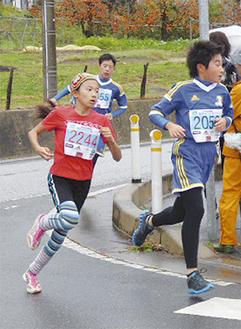 陸前高田市内のコースを駆け抜ける内田碧さん(左)