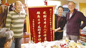 記念の旗が劉さん夫妻(左・中央)から加藤会長(右)へ贈られた