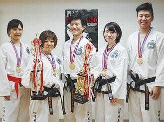 大会のトロフィーとメダルを手にする吉川さん、大島さん、中川さん、西村さん、青木さん(左から)