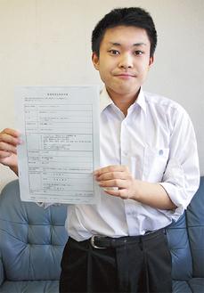 会社の登記簿謄本を手にする水島さん