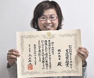 賞状を手に微笑む斉藤さん