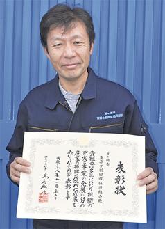賞状を手にする竹内理事長