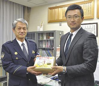 倉持署長(左)にカレンダーを手渡す趙組合長=12月5日・茅ケ崎警察署