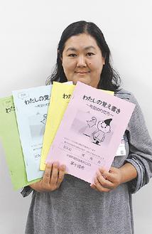「わたしの覚え書き」4冊セットを手にする市担当課職員