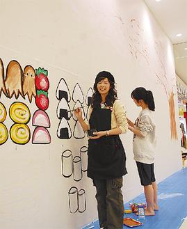 壁にアートを施した千葉和恵さんと娘の萌加さん(左から)=2月15日・イオン茅ヶ崎中央店