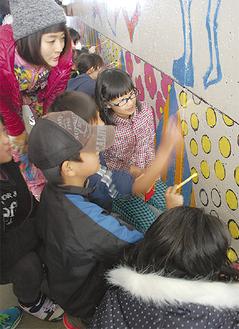 森さん(左)らの指導のもと、児童がペイント作業を進めた