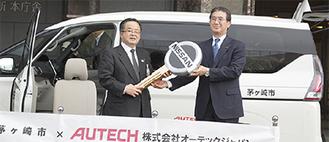 寄贈された特装車の前に立つ服部市長、片桐氏(左から)