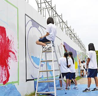 工事現場の仮囲いに絵を描く生徒たち