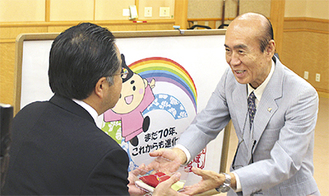 佐々木雅弘さん(右)が服部市長に鶴を手渡した