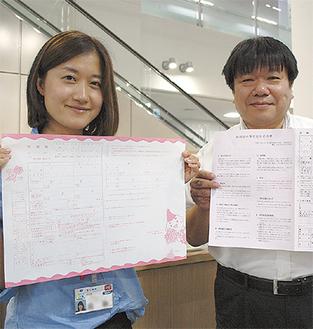 婚姻届(左)、書き方(右)を手にする市担当課職員