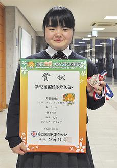 賞状とメダルを手にする山本さん