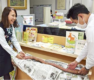 1m超えのサツマイモを展示する小出支店職員