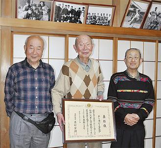 想い出の写真が飾られた部屋で文部大臣賞の賞状を持つ秋葉さん(中央)と田中さん(右)、長田さん(左)