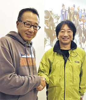 貫田さん(左)と握手を交わす九里さん