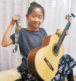 メダルを掲げる小橘田さんとギターに乗るピーちゃん