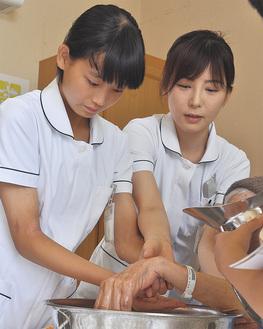 現役の看護師(右)から指導を受けた参加者