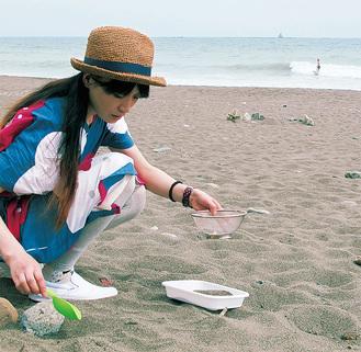 作品で使用する砂を茅ヶ崎海岸で採取する若見さん