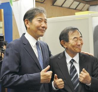 午後10時すぎに当選確実となり笑顔の佐藤氏(左)と野村後援会長