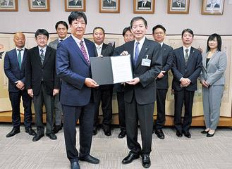 協定書を手にする森下代表(左)と佐藤市長