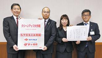 ごみ袋を掲げ持つ佐藤光市長(左)と江頭所長
