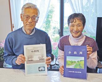 完成した記念誌を手に取る久子さん(右)と富雄さん
