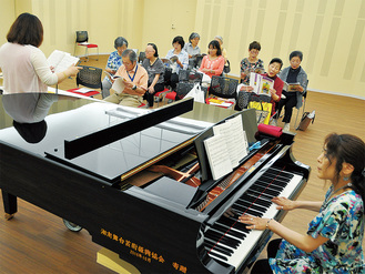 指導を受けながら歌う参加者たち
