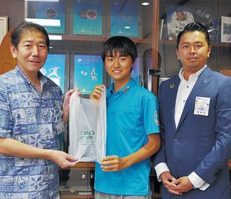 生分解性プラスチックを使ったビニール袋をもつ金丸さん(中央)と岡本理事長(右)、佐藤市長