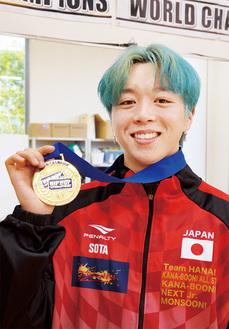 金メダルを持つ島雄さん