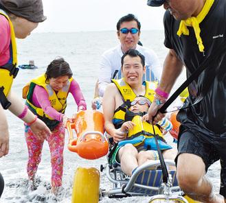 父親に抱えられ障害のある男の子も海に入った