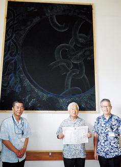 自身の作品の前に立つ臼井さん(中央)