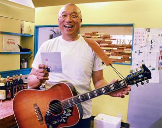 相棒のギターとCDを持つ平沼さん