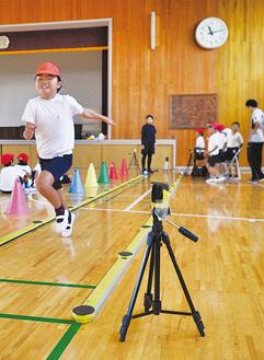 全力で走る児童。特殊な装置で走り方をデータ分析=松浪小