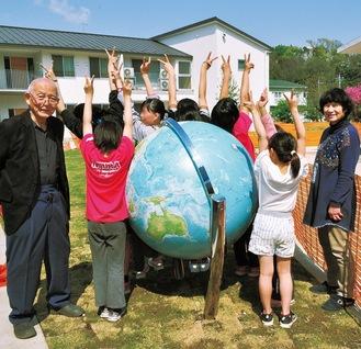 「背よりも大きいよ」と地球儀に喜ぶ子どもらと和田理事長・靖子夫人