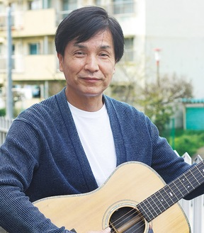 ギターを持ってほほ笑むKOICHIさん