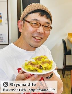 BISQの特製シュウマイを持ち、満面の笑みを浮かべるシュウマイ潤さん