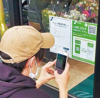 QRコードにスマホをかざし、アプリを登録する来店客