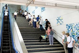 行列は駅自由通路から南口に向かう階段まで及んだ