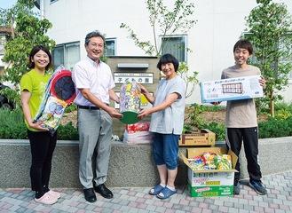 子どもの園で物品を手渡す藤江組合長(左から2人目)