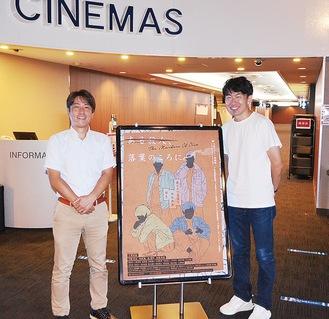 ポスターと並ぶ三澤監督(右)と鈴木総支配人