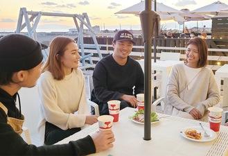 ▲友人らとカフェで語らう生駒夫妻(右)