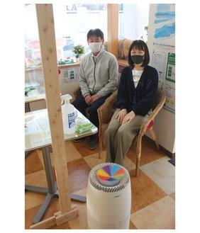 風車が回る空気洗浄機(手前)と不動産スタッフ(右が小川社長)