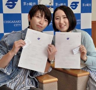 市発行の宣誓書受領証とカードを受け取り、喜びをかみ締める安田さんと大槻さん(右)