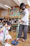 6年生が1年生の教室でそうじを手伝う
