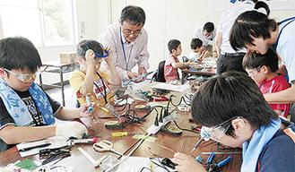 はんだごてを使ってロボットを作る子どもたち