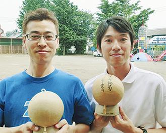 試作の募金箱を手にする磯川委員長(右)と山本毅事務局長