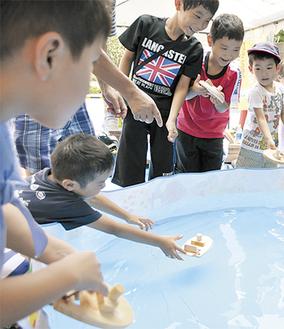 自作のゴム動力船で遊ぶ子どもたち