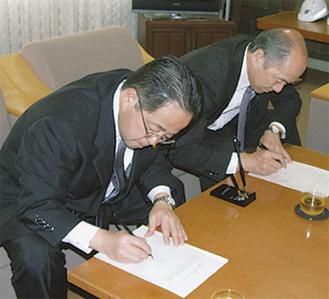 木村町長(右)と服部市長が協議書に調印した